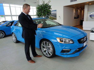 Will Routon, general manager of McDonald Volvo in Littleton, checks messages from 2016 Volvo V60 received via VolvoOnCall app on his smartphone. (Jan Wells photo)